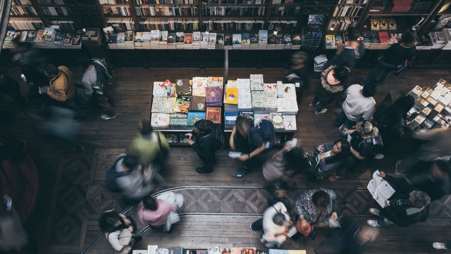 Cover Photo: This photograph looks down at the floor of a bookshop filled with customers browsing the shelves. Several people have been captured in motion, so their outlines are blurry, and there is a feeling of liveliness in the photo.