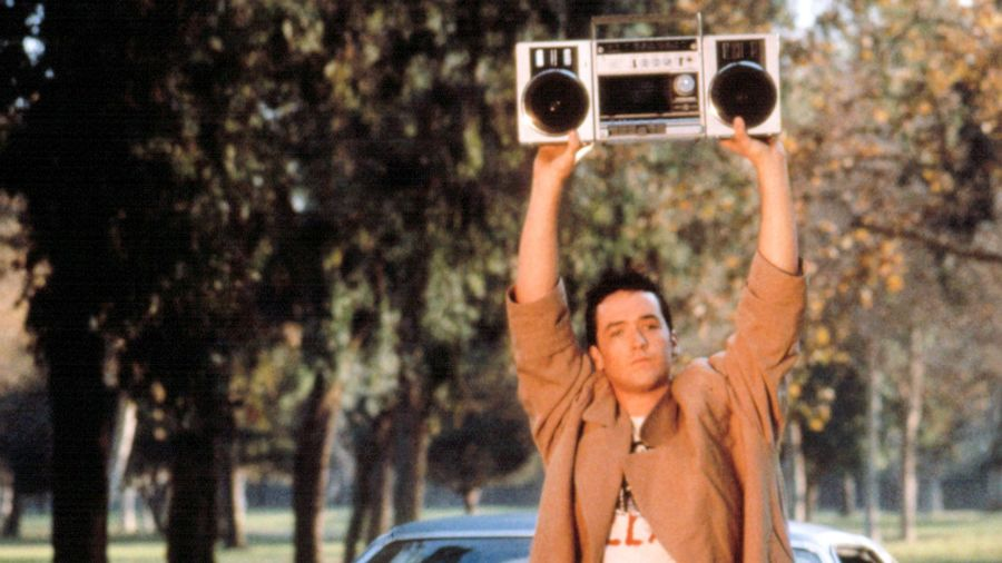 Cover Photo: A screencap from the 1989 film 'Say Anything,' in which the actor John Cusack, wearing a trench coat, lifts a boom box over his head.