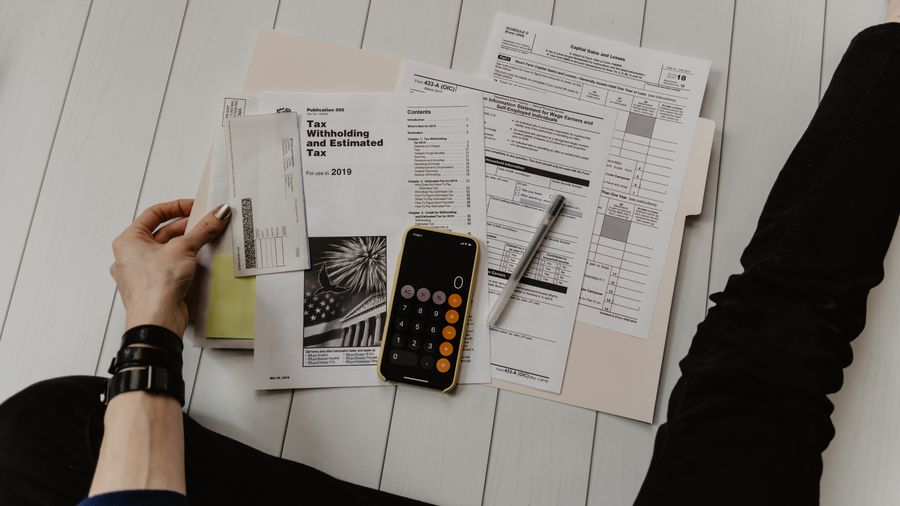 Cover Photo: This photograph shows a person with silver nail polish looking a tax documents spread out on white floorboards.