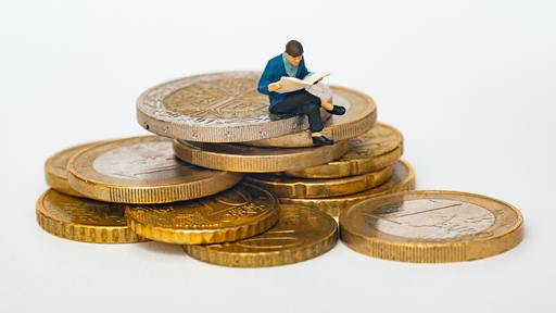 Cover Photo: This image shows a tiny figurine of a person sitting on top of a pile of gold coins. They are reading a book with their legs crossed.
