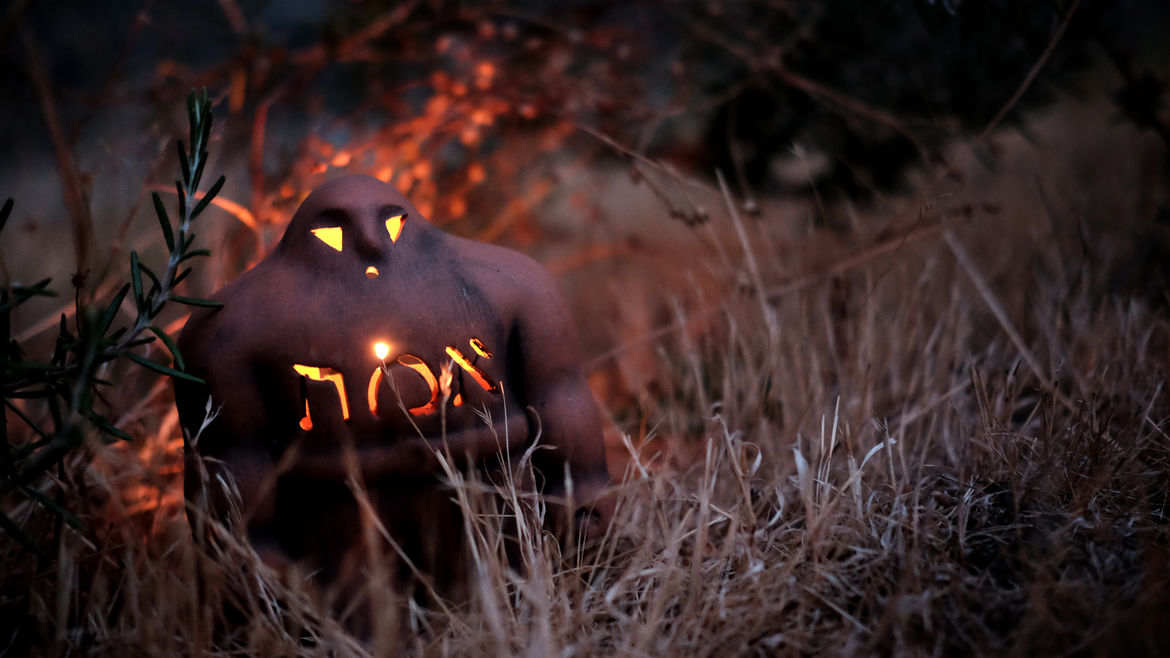 """Cover Photo: A photograph of the Golem, a small clay-fired figure with the Hebrew word for """"truth"""" carved into its chest, standing amidst dry grass illuminated from within by a candle."""