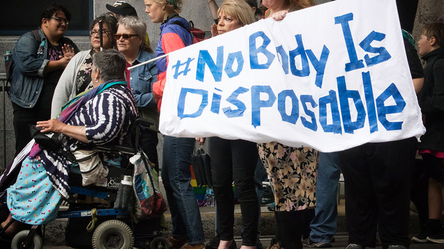 """Cover Photo: photograph from a protest centered on a person in a wheelchair, with short gray hair and a black and white striped top and blue skirt, to whose wheelchair is attached a sign reading """"#NoBodyIsDisposable"""""""