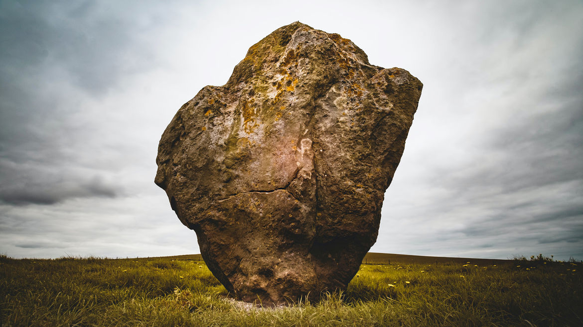 Cover Photo: A photograph of a large brown boulder sitting in the middle of a grassy field. The sky behind it is grey and cloudy.