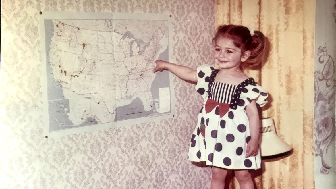 Cover Photo: A photograph of the author as a small child, wearing a dress and with her hair styled in pigtails. She is smiling and pointing at a map of the U.S. that is affixed to a wall.