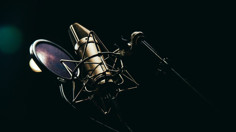 Cover Photo: A photograph of a studio microphone, on a microphone stand and with a filter in front of it, against a black background.