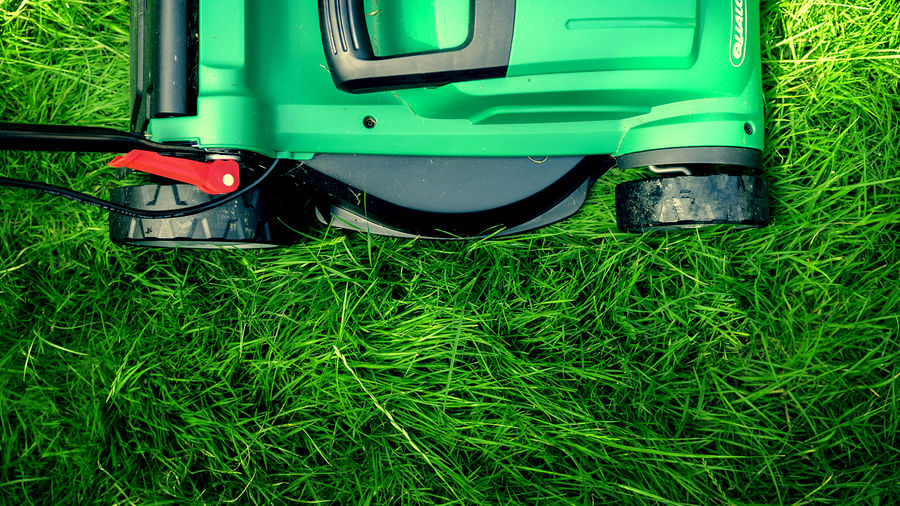Cover Photo: A photograph of the top of a bright green lawnmower atop a bed of bright green grass. The photo is cropped such that only half of the lawnmower top is visible.