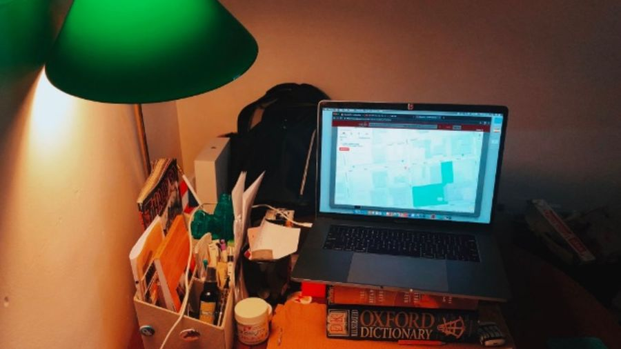 Cover Photo: This photograph shows a laptop poised on top of books above a messy desk with a green lamp that casts a warm yellow glow