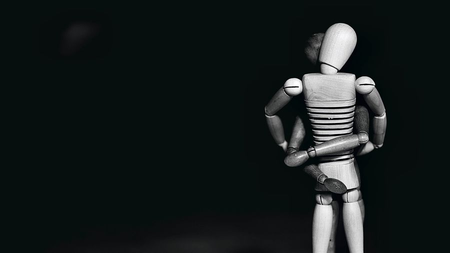 Cover Photo: This photograph is focused on two wooden drawing mannequins, which are standing and embracing. The background is black and the photo is in black and white with only the figurines illuminated