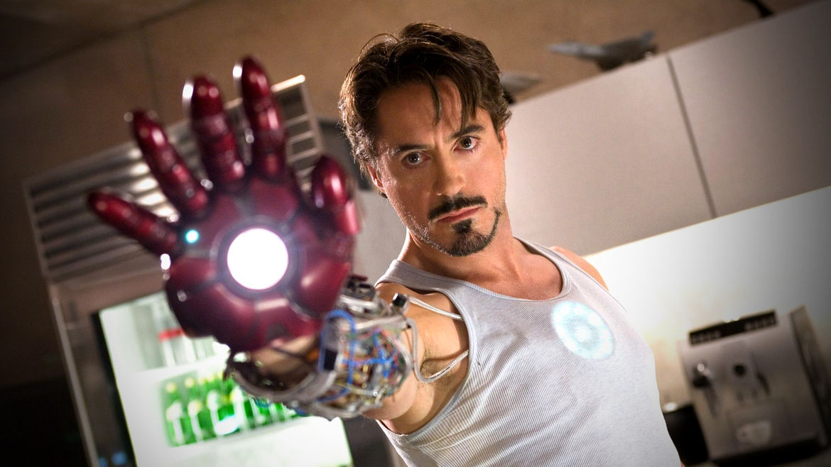 """Cover Photo: A production still of Robert Downey Jr. playing Tony Stark in the film """"Iron Man"""" (2008). He is wearing a white tank top and holding out his hand, which is encased in a dark red, mechanized metal glove."""