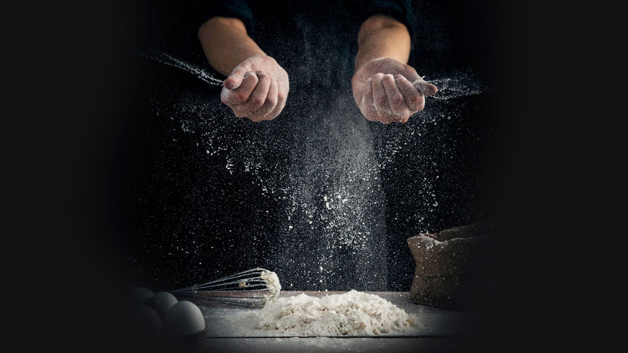 Cover Photo: A photograph of a baker's hands  over a pile of flour on a table. Grains of flour drift down from their hands into the pile. The table also contains some eggs, a whisk, and a bag of flour.