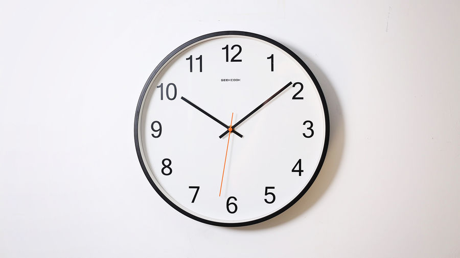 Cover Photo: A photograph of a white clock with black sans serif numbers, hanging on a white wall. The clock's hands are pointed at ten minutes past ten o'clock.