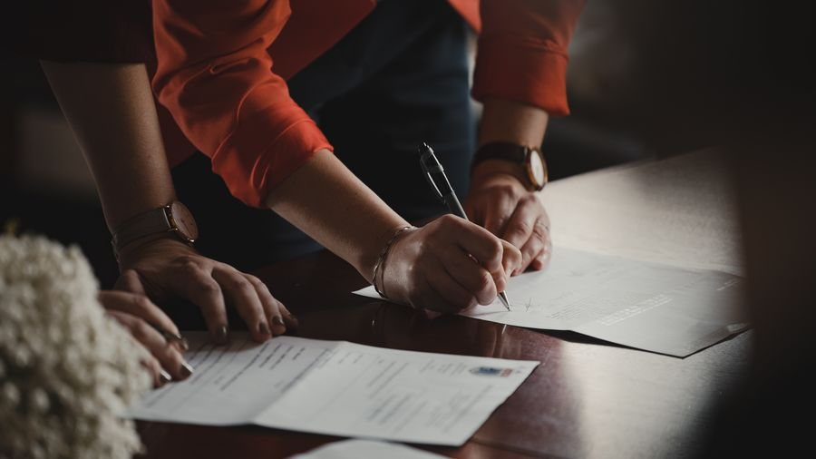Cover Photo: This photograph shows two people looking at some contracts on a table. One person is adding their signature with a pen.
