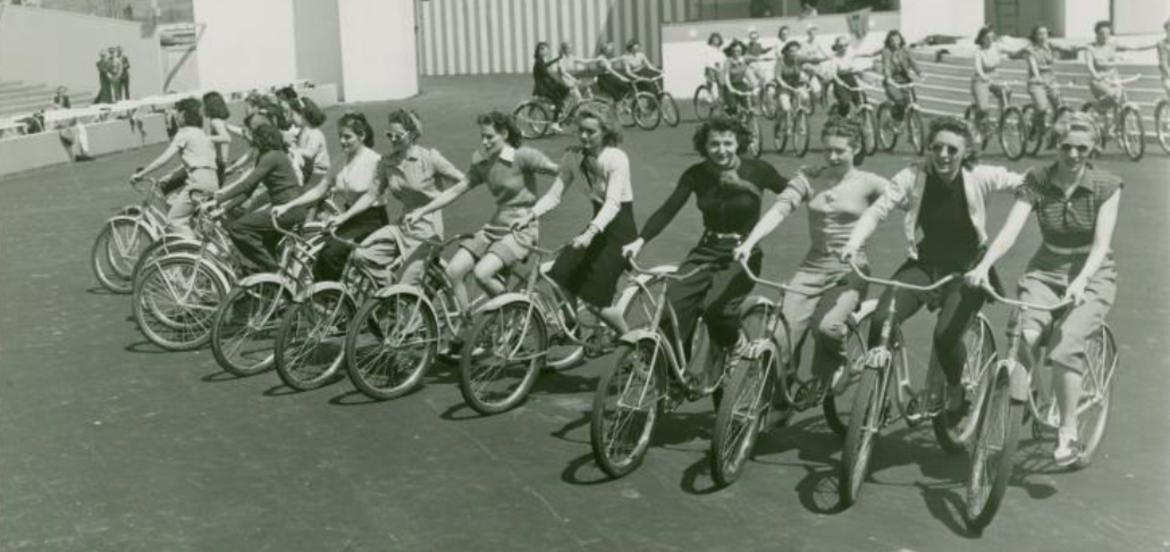 "Cover Photo:  ""Girls on bicycle during rehearsal"" via The New York Public Library Digital Collections. 1935 - 1945."