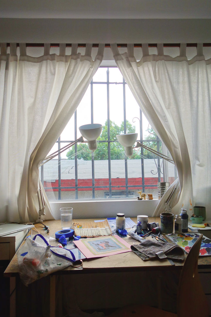 Photo of the artist's work desk, in front of a white-curtained window, surrounded by natural light and two lamps, with paints and supplies strewn throughout the desk space.