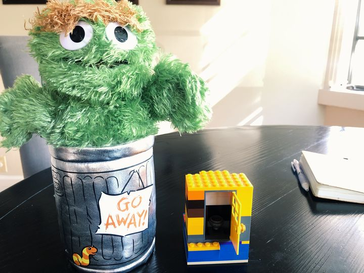 This picture shows a stuff Oscar the Grouch and his trash can next to a small lego structure