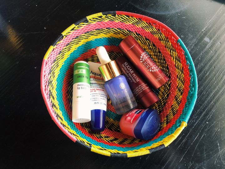 This photograph shows a colorful wire bowl filled with an assortment of different lip balms