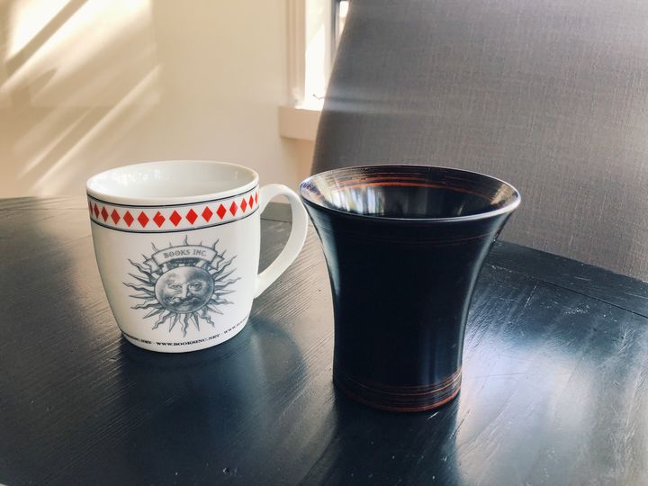 A picture of the author's mugs, one white with a large handle and a sun on the front and one a shiny black without a handle, whose bottom is more narrow than its top