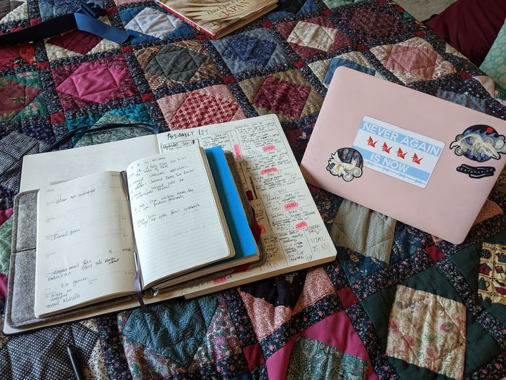 In this photograph, we see the author's notebooks, laptop, and a close-up of her quilt