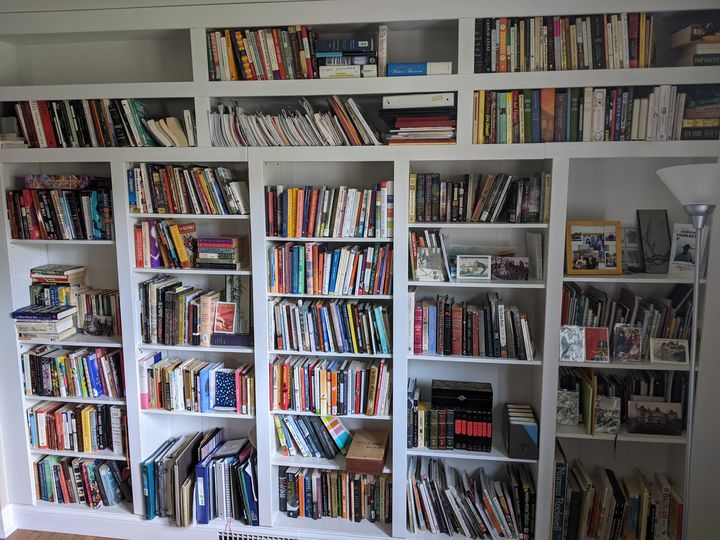 A photograph of the author's white, full-wall bookcase