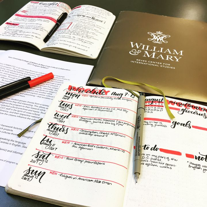 We see several journals spread out on a table, all designed with red marker. Also on the table is a folder for William & Mary University