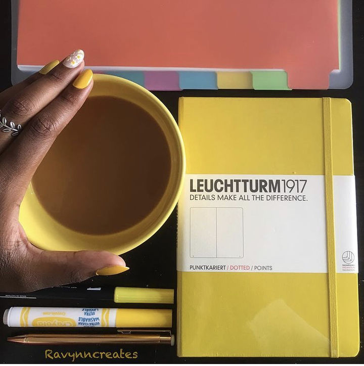 We see the author holding a yellow mug next to a yellow notebook and a color-coded file folder. The author's nails have yellow accents, too.
