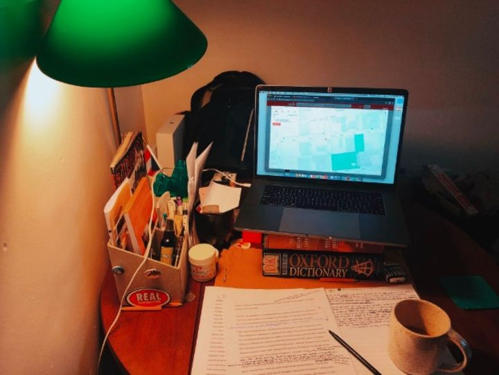 This photograph shows a laptop poised on top of books above a messy desk with a green lamp that casts a warm yellow glow