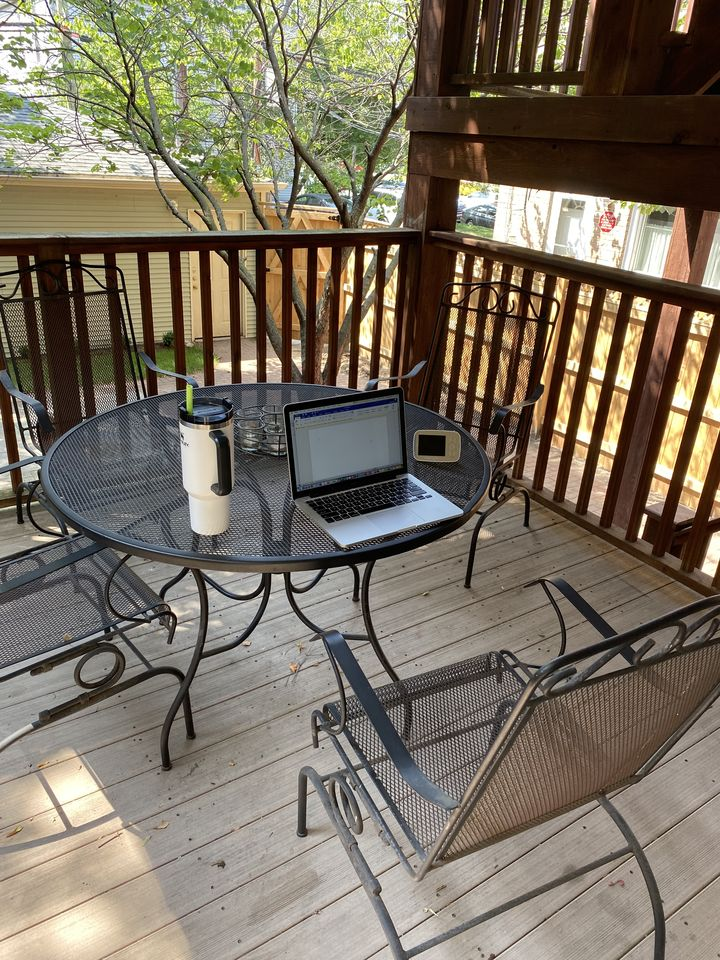 This picture shows the author's laptop perched on a patio table with a to-go cup of coffee sitting next to it. The day is sunny and spring-like.