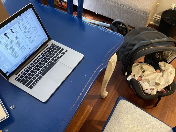 This photograph shows the author's laptop on a blue table with her baby sleeping in a baby carrier on the floor